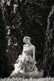 Schwarzweißfotografie des schönen Mädchens aufwerfend im Wald Stockbild