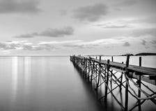 Schwarzweißfotografie eines hölzernen Piers des Strandes Stockbild