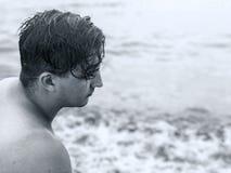 Schwarzweiss-Abschluss herauf Profil des jungen gut aussehenden Mannes auf dem Seehintergrund Nass gelocktes dunkles Haar Einsamk lizenzfreie stockbilder