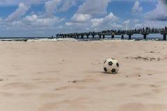 Schwarzweiss-Ball auf dem Strand Stockfotos