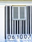 Schwarzweiss-Barcode gemalt auf einer Hausmauer mit einem Fenster in der Mitte Lizenzfreie Stockfotos