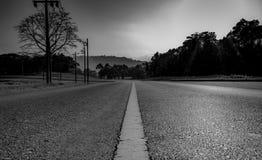 Schwarzweiss-Bild der Asphaltstraße in der Landschaft und im Wald neben der Straße Stockfotos