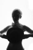 Schwarzweiss-Bild der Frau ihre Brüste mit einem Hut bedeckend lizenzfreies stockfoto