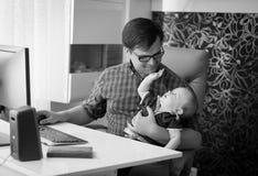 Schwarzweiss-Bild des lächelnden jungen Mannes, der im Innenministerium arbeitet und um seinen Babysohn sich kümmert lizenzfreies stockbild