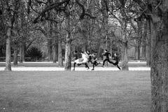 Schwarzweiss-Bild einer Gruppe Kinder, die in einen Park laufen Stockbild