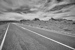 Schwarzweiss-Bild einer Wüstenstraße, USA Stockbild
