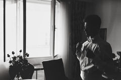 Schwarzweiss-Bild eines Mannes, der sein Hemd hinter einem Br justiert Lizenzfreies Stockbild
