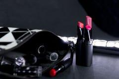 Schwarzweiss bilden Sie Tasche mit Satz Lippenstiften Mode bunt Berufsmake-upschönheit Blinken bokeh Hintergrund Stockbilder