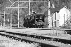 Schwarzweiss-Blockwagen auf Eisenbahn durch Obertraun-Dorf Stockbilder