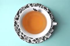 Schwarzweiss-Blumenporzellanteeschale mit Tee auf Draufsicht des Pastellhintergrundes mit Kopienraum Lizenzfreie Stockfotografie