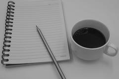Schwarzweiss-Farbton-Kaffeetasse mit Buch für Hintergrund Stockfotografie