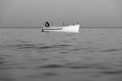 Schwarzweiss-Fischerboot im Wasser des ruhigen Sees im Sonnenunterganglicht Lizenzfreie Stockfotografie