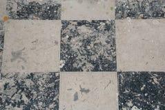 Schwarzweiss-Fliesenboden befleckt stockfotos