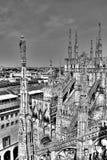 Schwarzweiss-Foto der Marmorstatuen, der Helme und der Steinskulpturen auf dem Dach des berühmten Kathedralenduomo und -Stadtbild Stockfotos