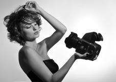 Schwarzweiss-Foto der schönen Modefrau, Modell aufpassend auf Fotokamera Lizenzfreie Stockfotografie