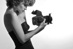 Schwarzweiss-Foto der schönen Modefrau, Modell aufpassend auf Fotokamera Lizenzfreie Stockfotos