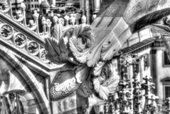 Schwarzweiss-Foto der weißen Marmorstatuen, der Helme und der Steinskulpturen auf dem Dach berühmten Kathedrale Duomo Stockfoto