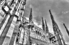 Schwarzweiss-Foto der weißen Marmorstatuen, der Helme und der Steinskulpturen auf dem Dach berühmten Kathedrale Duomo Lizenzfreies Stockfoto