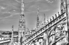 Schwarzweiss-Foto der weißen Marmorstatuen, der Helme und der Steinskulpturen auf dem Dach berühmten Kathedrale Duomo Lizenzfreie Stockfotos