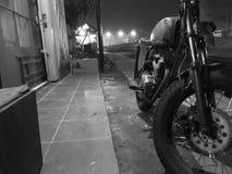 Schwarzweiss-Foto des alten Motorrades geparkt vor der Tür lizenzfreies stockbild