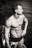 Schwarzweiss-Foto des attraktiven muskulösen jungen Mannes durch das Meer Lizenzfreie Stockfotos