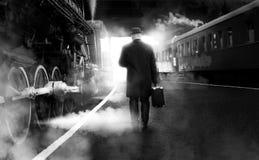 Schwarzweiss-Foto des Mannes in der Weinlese kleidet das Gehen auf railw stockbilder