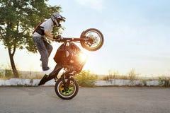 Schwarzweiss-Foto des Radfahrers springt auf Motorrad beim Reiten Stockfotos