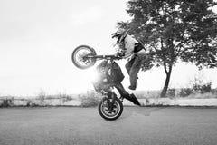 Schwarzweiss-Foto des Radfahrers springt auf Motorrad beim Reiten Stockbilder