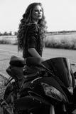 Schwarzweiss-Foto eines schönen Radfahrermädchens mit einem Motorrad lizenzfreie stockbilder