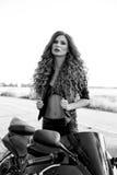 Schwarzweiss-Foto eines schönen Radfahrermädchens mit einem Motorrad stockfotografie