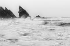 Schwarzweiss-Foto felsiger Küstenlinie Atlantiks Stockfotografie