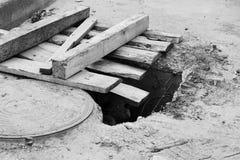 Schwarzweiss-Foto Loch im Boden mit Brettern nahe bei der Luke im Parkplatz nahe dem Speicher Lizenzfreies Stockbild