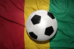Schwarzweiss-Fußballball auf der Staatsflagge der Guine stockbild