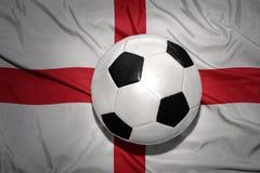 Schwarzweiss-Fußballball auf der Staatsflagge von England Stockfoto