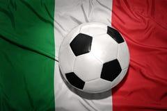 Schwarzweiss-Fußballball auf der Staatsflagge von Italien Stockfotografie