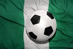 Schwarzweiss-Fußballball auf der Staatsflagge von Nigeria Stockbild