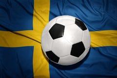 Schwarzweiss-Fußballball auf der Staatsflagge von Schweden Lizenzfreies Stockbild