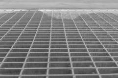 Schwarzweiss, Gitter für Wasserentwässerung vor dem entr Stockbild