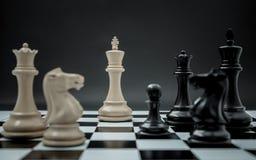 Schwarzweiss-König und Ritter des Schachs gründeten auf dunklem backgroun Stockfoto