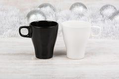 Schwarzweiss-Kaffeetassen auf weißem hölzernem Hintergrund mit Weihnachtsdekoration Bechermodell Lizenzfreies Stockbild