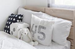Schwarzweiss-Kissen mit Puppe auf hölzernem Bett im Schlafzimmer des Kindes stockfotografie