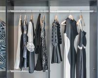 Schwarzweiss-Kleidung, die im Wandschrank hängt stockfotografie