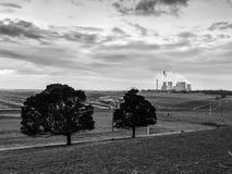 Schwarzweiss-Kohleenergieelektrizitätswerk, das Gasrauch an den bewölkten blauen Himmel abgibt lizenzfreies stockfoto