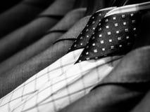 Schwarzweiss Männer ` s von Hemden und von Anzug, die am Gestell hängen Lizenzfreies Stockbild