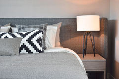 Schwarzweiss-Muster pillows mit grauer Decke und weißer Tischlampe Stockfotos