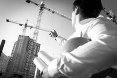 Schwarzweiss-Nahaufnahme des Ingenieurs zeigend auf das Gebäude lizenzfreies stockbild