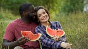 Schwarzweiss-Paare, die sich amüsieren und köstliche Wassermelone essen stockfotos