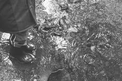 Schwarzweiss-Pfützen mit Regenstiefeln Lizenzfreies Stockfoto