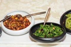 Schwarzweiss-Platte mit verschiedenen frischen Salaten auf dem Tisch Stockbild