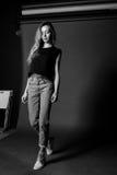 Schwarzweiss-Porträt des blonden Mädchens im T-Shirt und in den Jeans gegen einen dunklen Hintergrund, der den Schritt, Modellver Lizenzfreie Stockfotografie